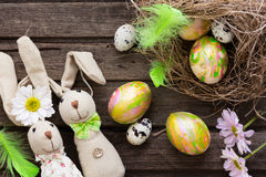 Easter background with colorful eggs in nest and home made banni Royalty Free Stock Photos
