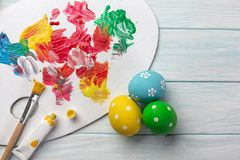 Easter background with colorful eggs, paints, brushes on stone gray. Top view with copy space.  royalty free stock photos
