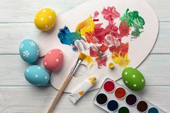 Easter background with colorful eggs, paints, brushes on stone gray. Top view with copy space.  stock photography