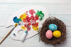 Easter background with colorful eggs, paints, brushes on stone gray. Top view with copy space.  royalty free stock image