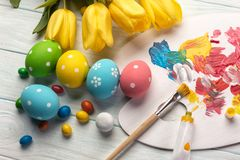 Easter background with colorful eggs, paints, brushes on stone gray. Top view with copy space.  stock photos