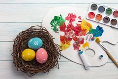 Easter background with colorful eggs, paints, brushes on stone gray. Top view with copy space.  stock image