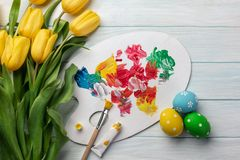 Easter background with colorful eggs, paints, brushes and yellow tulips on wooden table. Top view with copy space.  stock image