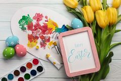 Easter background with colorful eggs, paints, brushes and yellow tulips on wooden table. Top view with copy space.  stock photography