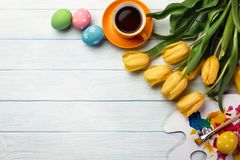Easter background with colorful eggs, paints, brushes and yellow tulips on wooden table. Top view with copy space.  stock photo