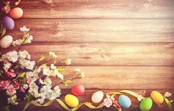 Easter background with colorful eggs and spring flowers. Top view with copy space stock image