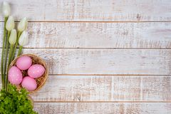 Colorful easter eggs and tulips over white wooden table Royalty Free Stock Photo