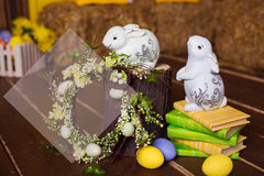 Easter background with colorful eggs, white bunny and yellow flowers over old wood. Top view with copy space Stock Photos
