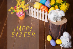 Easter background with colorful eggs, white bunny and yellow flowers over old wood. Top view with copy space Stock Photo