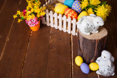 Easter background with colorful eggs, white bunny and yellow flowers over old wood. Top view with copy space Royalty Free Stock Photography