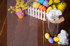 Easter background with colorful eggs, white bunny and yellow flowers over old wood. Top view with copy space Stock Image