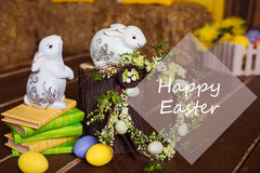 Easter background with colorful eggs, white bunny and yellow flowers over old wood. Top view with copy space Royalty Free Stock Image