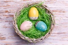 Top view of Easter eggs in a wicker basket on a wooden background. Easter holidays concept. Royalty Free Stock Images