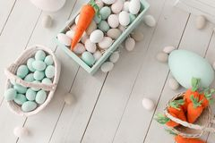 Easter background with colorful eggs and yellow orange carrots over white wood. Top view with copy space.  stock image