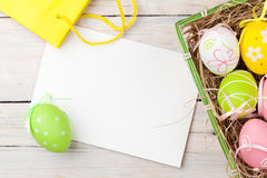 Easter background with colorful eggs, yellow tulips and greeting Stock Images
