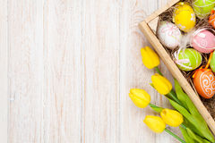 Easter background with colorful eggs and yellow tulips. Over white wood. Top view with copy space Stock Photo