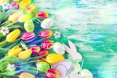 Easter background with colorful eggs and yellow tulips over wood stock image