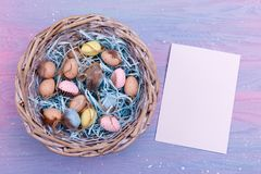 Easter background with colorful quail eggs, feathers in a wicker basket and an empty paper near it, top view. Copy space Stock Photos
