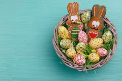 Top view of Easter quail eggs and cookies shaped like a bunny in a wicker basket on a blue background. Stock Photography