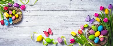 Easter background. Colorful spring tulips with butterflies and p. Ainted eggs on vintage wooden board