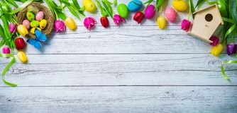 Easter background. Colorful spring tulips with butterflies and p. Ainted eggs on vintage wooden board royalty free stock images