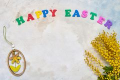Easter background. Easter decoration, mimosa flowers and colorful letters forming words HAPPY EASTER. Copy space for your text. Flat lay of Easter celebration stock photos