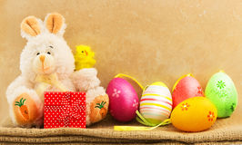 Easter background of decorative bunny toy, color easter eggs and chicken Stock Photography