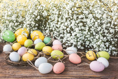 Easter background with decorative colorful eggs and white gipsophila flowers. Toned Stock Image