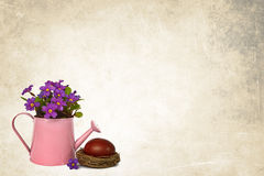 Easter background: Easter egg and primrose flowers arranged in watering bucket Royalty Free Stock Photo