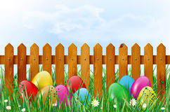 Easter background with easter eggs in grass and wooden fence. Easter background with easter eggs, wooden fence, sky, grass, and flowers. Vector illustration Royalty Free Stock Photos