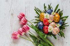 Easter Background with easter eggs and pink tulips on light wooden background. flower arrangement in the form of a nest Stock Image