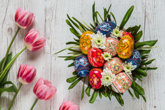 Easter Background with easter eggs and pink tulips on light wooden background. flower arrangement in the form of a nest Stock Photo