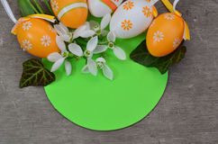 Easter background with Easter eggs and snowdrops. Easter background with Easter eggs and snowdrop flowers on green rounded shape stock photo