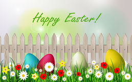 Easter background with easter eggs. White wooden fence sky grass and flowers Royalty Free Stock Images