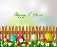 Easter background with easter eggs. Wooden fence sky grass and flowers Royalty Free Stock Image