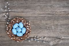 Easter background. Easter willow wreath and blue Easter eggs on old wooden  background. Top view, copy space. Greeting card Stock Photos