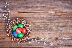 Easter background. Easter willow wreath and colorful Easter eggs on old wooden background. Top view, copy space. Holiday background Royalty Free Stock Photos