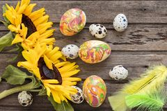 Easter background with eggs, flowers, and decoration on wooden board, top view.  royalty free stock photo