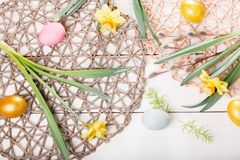 Easter background with Easter eggs and spring flowers. Top view with copy space. Easter background with Easter eggs, pussy-willow and spring flowers narcissus royalty free stock images