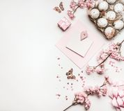 Easter background with flat lay of eggs,gifts, decorations blossom and blank greeting card mock up. On white desktop, top view, pink pastel color stock images