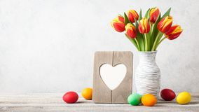 Easter background with fresh tulips and painted eggs stock images