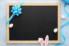Easter background with funny bunny ears, chalkboard and ribbon stock photography