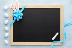 Easter background with funny bunny ears, chalkboard and ribbon royalty free stock images