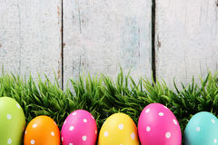 Easter background with grass. Easter eggs on wood backgrpund Stock Photo