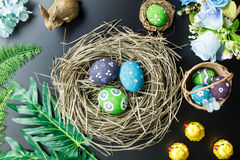 Easter background.Happy easter eggs pained also rabbin. Top view Easter background.Happy easter eggs pained also rabbin and cross on nest.Texture black wooden Royalty Free Stock Photo