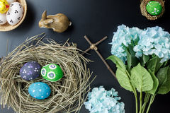 Easter background.Happy easter eggs pained also rabbin. Top view Easter background.Happy easter eggs pained also rabbin and cross on nest.Texture black wooden Stock Photography