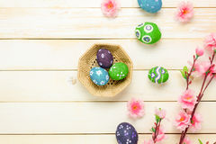 Easter background.Happy easter eggs pained on basket al. Top view easter background.Happy easter eggs pained on basket also beautiful pink flower.Texture rustic Stock Image