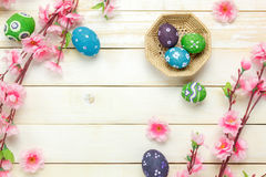 Easter background.Happy easter eggs pained on basket al. Top view easter background.Happy easter eggs pained on basket also beautiful pink flower.Texture rustic Royalty Free Stock Image