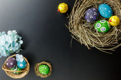 Easter background.Happy easter eggs pained on nest also. Top view Easter background.Happy easter eggs pained on nest also beautiful flower.Texture balck wooden Royalty Free Stock Images