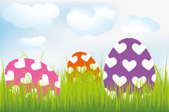 Easter background with heart-decorated eggs in meadow Stock Image